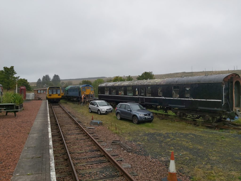 Train carriages with men working on them, cars parked nearby