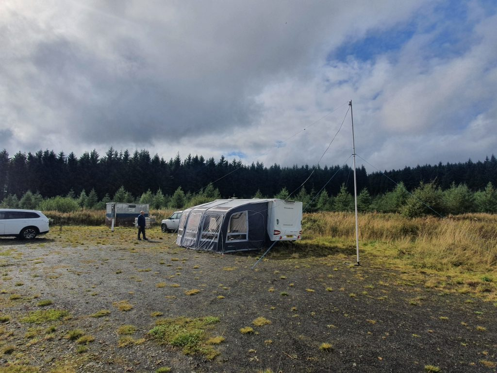 Station caravan and awning with antenna overhead, Dave S standing nearby