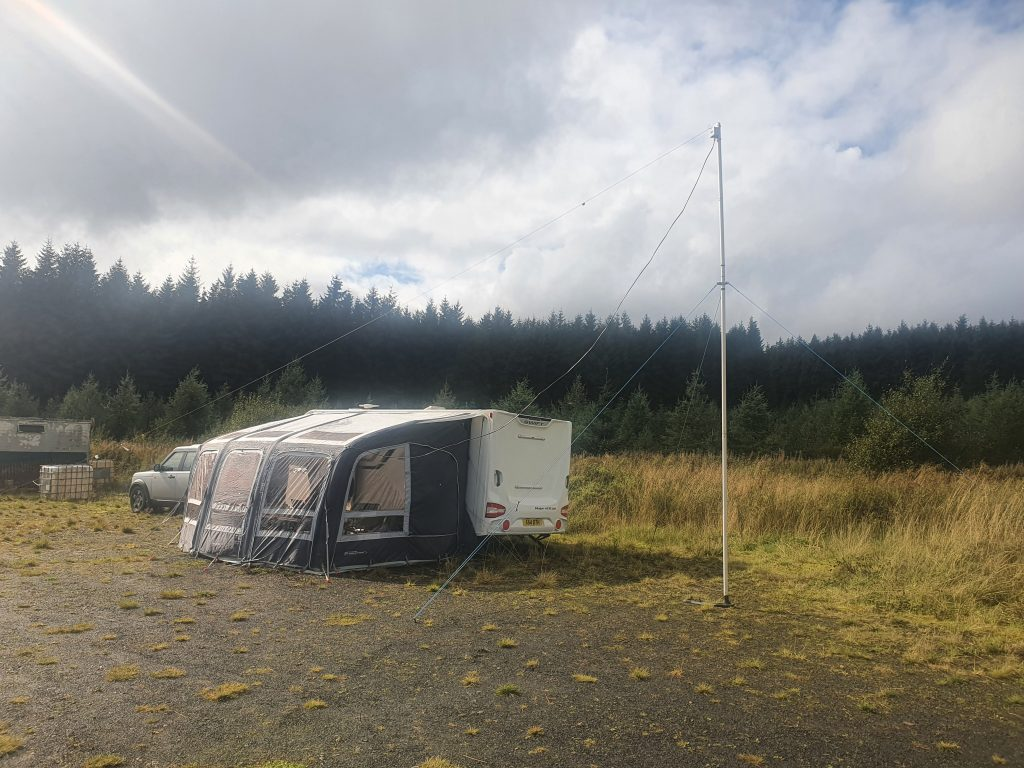 Station caravan with awning, antenna reaching overhead